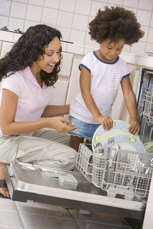 domestic chore: Mother And Daughter Loading Dishwasher Stock Photo