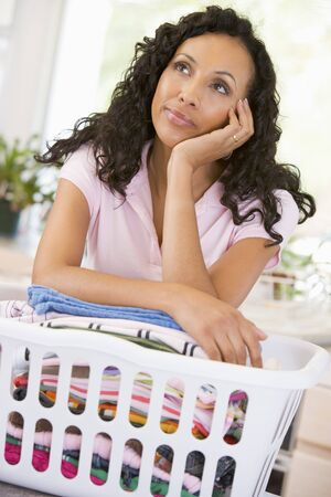Woman Daydreaming Over Washing Basket  photo