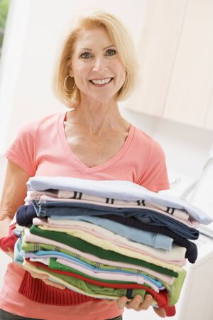 Woman Carrying Folded Up Laundry photo