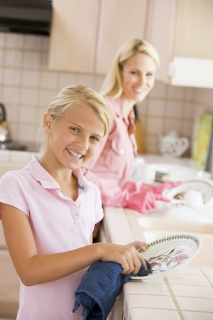 dish washing gloves: Mother And Daughter Cleaning Dishes Stock Photo