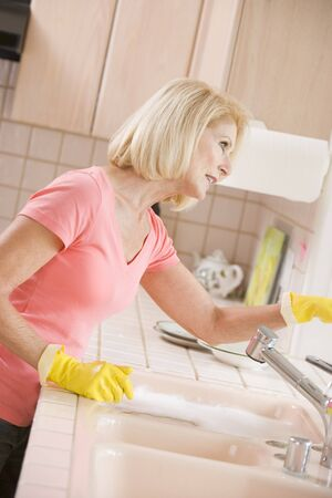 kitchen counter: Woman Cleaning Kitchen Counter Stock Photo