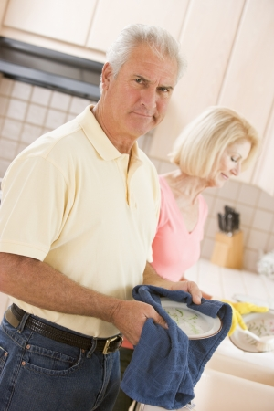Husband And Wife Cleaning Dishes photo
