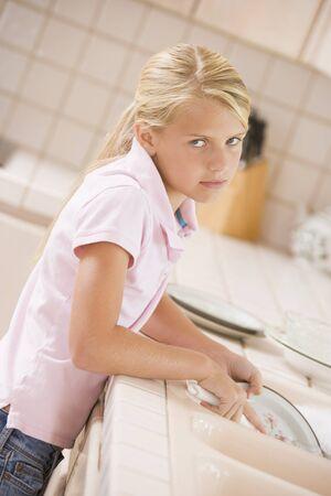gente triste: Chica joven, limpieza de platos,  Foto de archivo