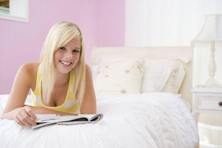 leggere rivista: Teenage Girl disteso sul letto della lettura