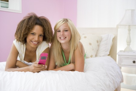 Teenage Girls Lying On Bed Using Cellphone  photo