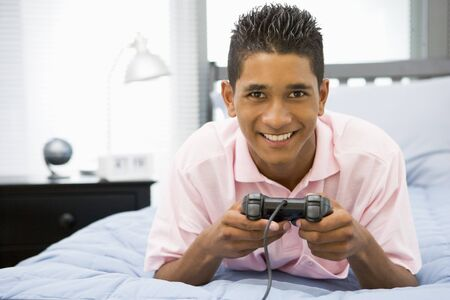 Teenage Boy Lying On Bed Playing Video Game photo