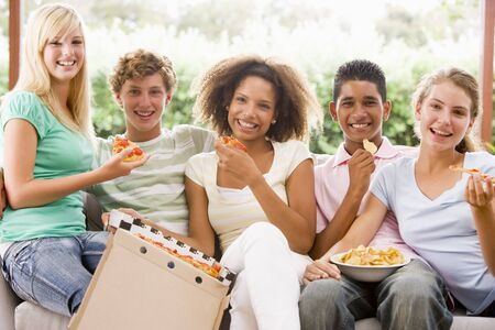 Group Of Teenagers Sitting On A Couch Eating Pizza photo