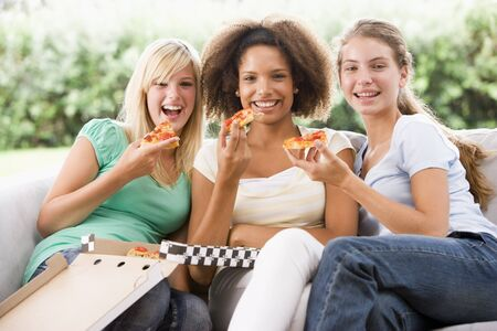 Teenage Girls Sitting On Couch And Eating Pizza Together photo