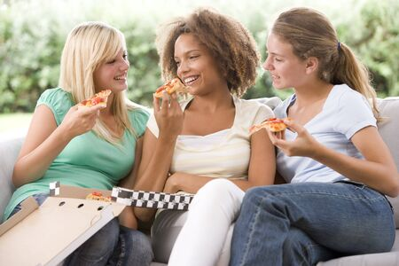 Teenage Girls Sitting On Couch And Eating Pizza Together Stock Photo - 4446361