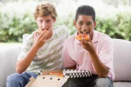boy 15 year old: Teenage Boys Sitting On Couch Eating Pizza Together