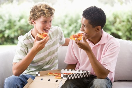 Teenage Boys Sitting On Couch Eating Pizza Together photo