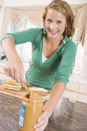 Teenage Girl Making Peanut Butter Sandwich photo