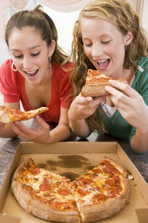 16 year old girls: Teenage Girls Eating Pizza  Stock Photo