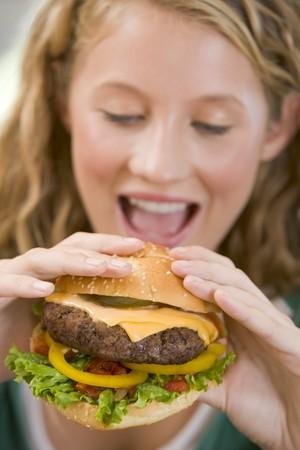beefburger: Teenage Girl Eating Burgers  Stock Photo