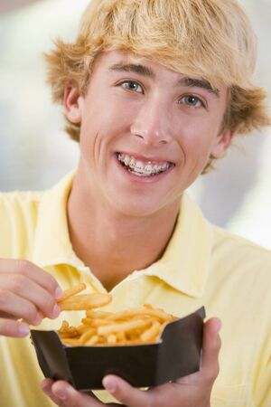 Teenage Boy Eating French Fries Stock Photo - 4445014