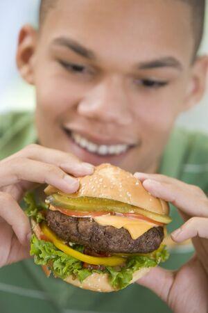 Teenage Boy Eating Burger Stock Photo - 4445340