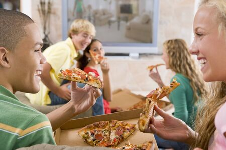 Teenagers Hanging Out In Front Of Television Eating Pizza  Stock Photo - 4447002