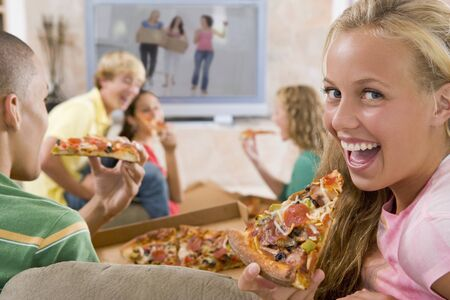 Teenagers Hanging Out In Front Of Television Eating Pizza  photo