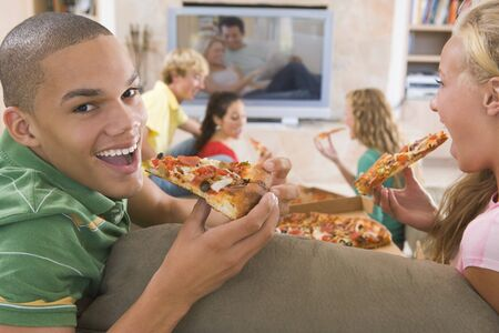 16 year old girls: Teenagers Hanging Out In Front Of Television Eating Pizza