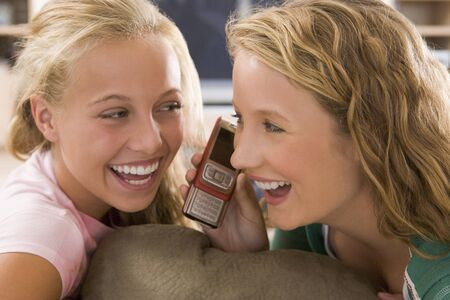 Teenagers Hanging Out In Front Of Television Using Mobile Phones  photo