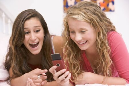 Teenage Girls Lying On Bed Using Mobile Phone photo