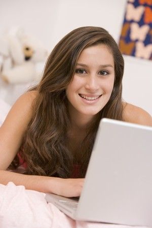 Teenage Girl Lying On Her Bed Using Laptop photo
