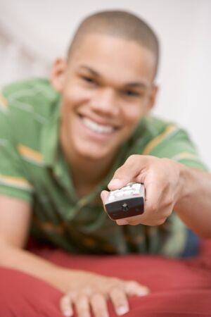 Teenage Boy Lying  On Bed Using Remote Stock Photo - 4446667