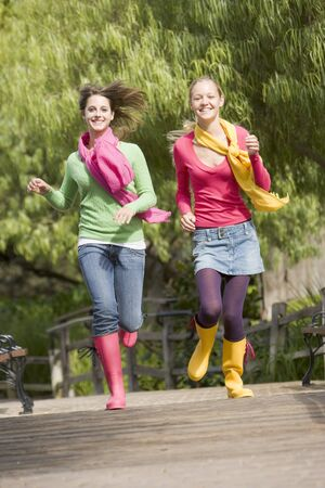 Pair Of Teenage Girls Jogging In Park  photo