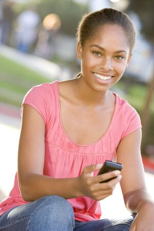 Teenage Girl Sitting Outdoors Using Mobile Phone photo