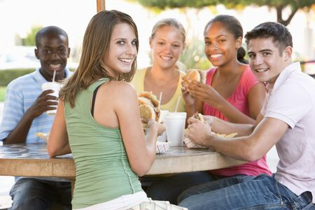 fast eat: Group Of Teenagers Sitting Outdoors Eating Fast Food