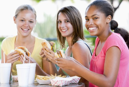 16 year old girls: Teenage Girls Sitting Outdoors Eating Fast Food