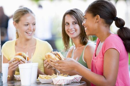Teenage Girls Sitting Outdoors Eating Fast Food  Stock Photo - 4446901