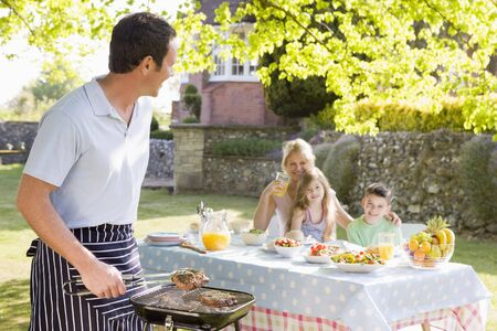 home garden: Family Enjoying A Barbeque Stock Photo