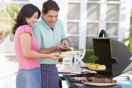 Couple Cooking On A Barbeque Stock Photo - 4506890
