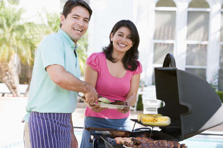 Couple Cooking On A Barbeque photo