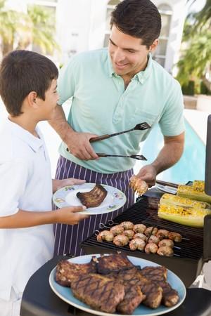 hombre cocinando: Padre e hijo Barbequing