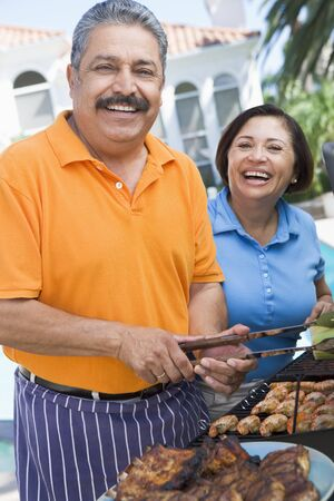 american seniors: Couple Cooking On A Barbeque Stock Photo