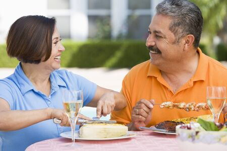 Couple Enjoying A Barbequed Meal In The Garden photo