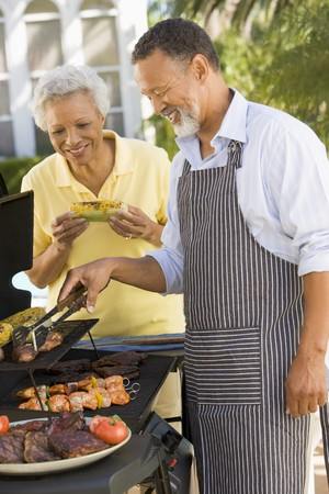 Couple Cooking On A Barbeque Stock Photo - 4507148