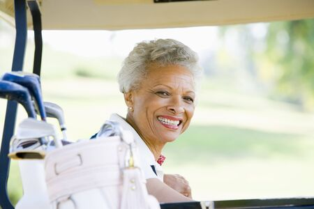 golf cart: Portrait Of Woman Sitting In A Golf Cart Stock Photo
