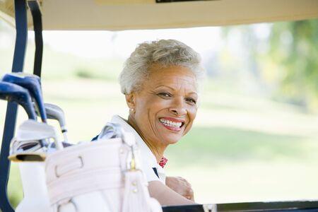 one senior adult woman: Retrato de una mujer sentada en un carrito de golf