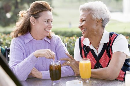 Two Female Friends Enjoying A Beverage By A Golf Course Stock Photo - 4507144