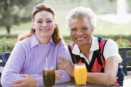 Two Female Friends Enjoying A Beverage By A Golf Course Stock Photo - 4507120