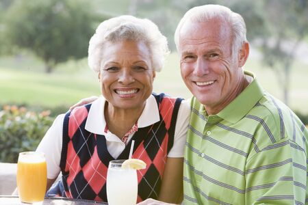 Couple Enjoying A Beverage By A Golf Course Stock Photo - 4507113