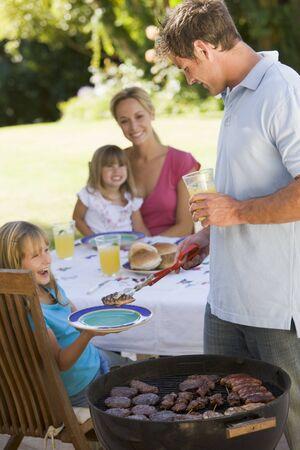 happy family garden: Family Enjoying A Barbeque Stock Photo