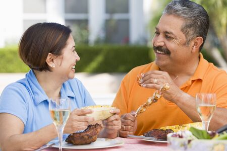 Couple Enjoying A Barbequed Meal In The Garden Stock Photo - 4507373