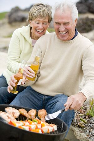 Couple Cooking On A Barbeque Stock Photo - 4507580