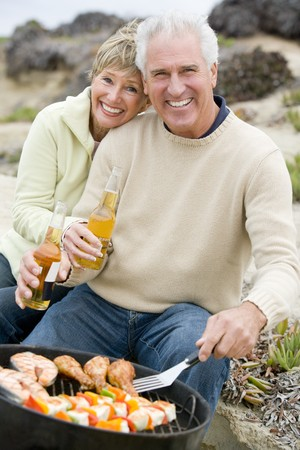 Couple Cooking On A Barbeque Stock Photo - 4507586