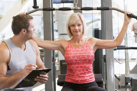 Personal Trainer Watching Woman Weight Train photo
