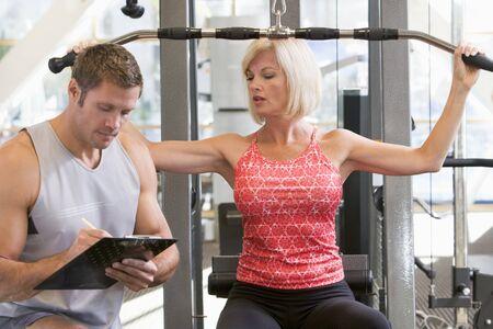 aide � la personne: Personal Trainer Watching Femme Poids Train Banque d'images
